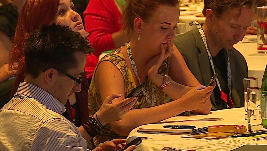 publiek stemt met stemkastje bij hybride evenement moderator